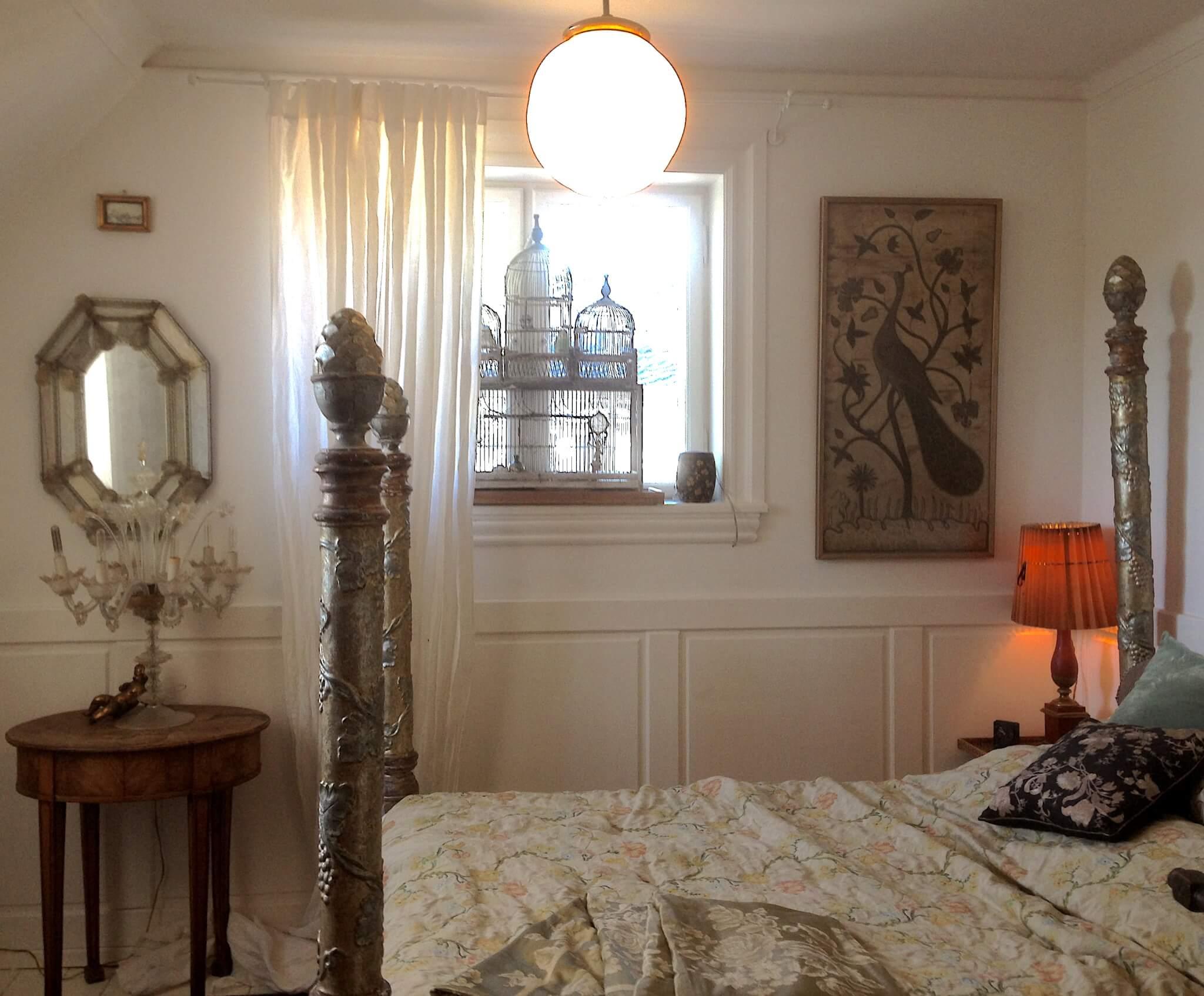 Soveværelse med venetiansk seng, lampe og spejl
